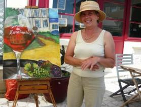 Bridget with her painting of her wine domain, la Domaine d'Enchantoir